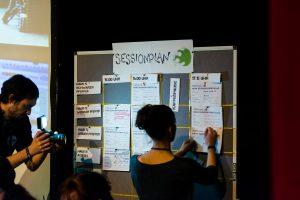 Menschen an der Pinnwand bei der Sessionplanung